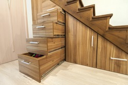 Modern architecture interior with  luxury hallway with glossy wooden stairs in modern storey house. Custom built pullout cabinets on glides in slots under stairs. Use of space for storage.