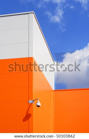 Modern architecture - orange building with security camera against blue sky. Detail photography.