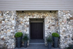 Modern architecture. Residential facade design. Closeup view of new house iron front door, stonewall and decorative plant Buxus sempervirens, also known as boxwood bush, growing in pots.