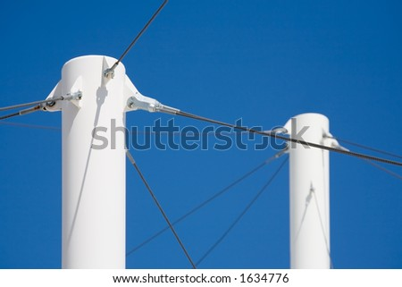 modern architecture - white pillars with steel cables supporting the roofing against blue sky