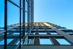 Modern architecture with glass facade under blue sky.