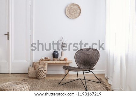 Modern armchair and pouf on brown carpet in white apartment interior with door. Real photo #1193167219