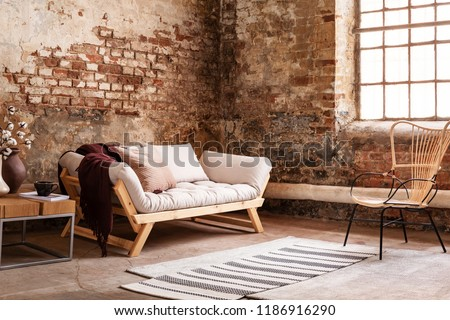 Modern armchair next to grey sofa in loft interior with window and red brick wall. Real photo