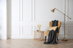 Modern armchair with soft blanket, coffee table and lamp in stylish room interior. Space for text