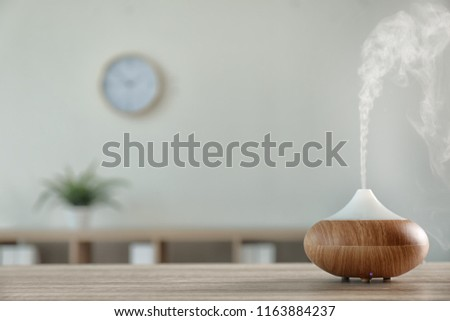 Modern aroma lamp on table against blurred background with space for text #1163884237