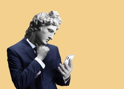 Modern art collage. Concept portrait of a  businessman  holding mobile smartphone using app texting sms message. Gypsum head of of Apollo. Man in suit.