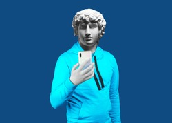 Modern art collage. Concept portrait of a man  holding mobile smartphone using app texting sms message. Gypsum head of Antinous. Man in suit. On a blue background.