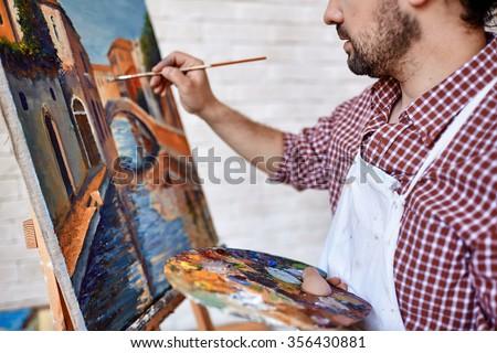 Modern artist painting landscape with oilpaints