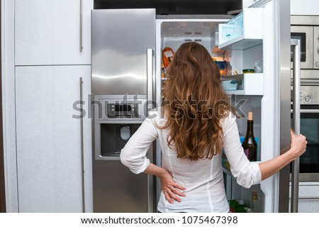 Modern attractive woman with long hair standing in the kitchen opening the frige door and looking inside.