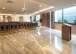 Modern auditorium interior with lecturer desk and rows of vintage chairs in luxury training center. Educational class background with copy space