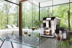 Modern automatic coffee machine on a glass table in a modern interior