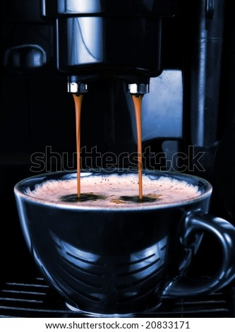 Modern automatic espresso machine pouring the perfect cup of black coffee.  Slick dark lighting to match the cup and machine coloring and convey sophistication.