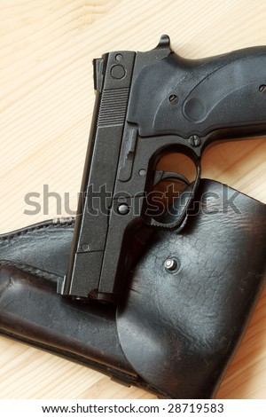 Modern automatic pistol and old leather holster on wooden background