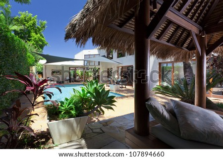 Modern backyard with swimming pool and Bali hut in Australian mansion - stock photo