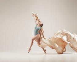 Modern ballet dancer exercising in full body on white studio background. Ballerina or female dancer with silk fabric dancing on white studio background. Caucasian model on pointe shoes