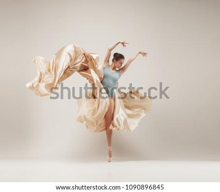 Modern ballet dancer exercising in full body on white studio background. Ballerina or female dancer with silk fabric dancing on white studio background. Caucasian model on pointe shoes #1090896845