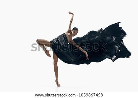 Modern ballet dancer exercising isolated in full body on white studio background. Ballerina or modern dancer in black silk dress dancing on white studio background. Caucasian model dancing barefoot