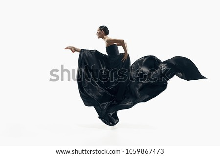 Modern ballet dancer exercising isolated in full body on white studio background. Ballerina or modern dancer in black silk dress dancing on white studio background. Caucasian model dancing barefoot #1059867473
