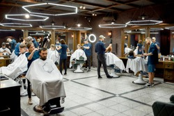 Modern barbershop. Professional barbers serving clients in the modern loft style barber shop. General view. Hairdresser services. Barbershop interior. Hair cutting, hairdressing, shaving, grooming