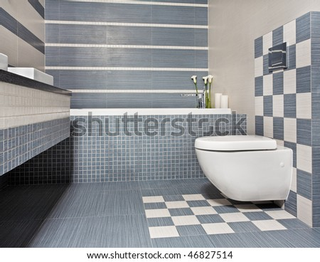 Modern bathroom in blue and gray tones with toilet and mosaic