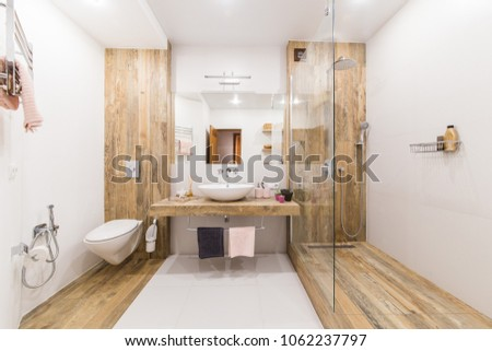 Modern bathroom interior combined with toilet. Shower room and toilet are covered with tiles in the color of wood, white walls and a white floor and a washbasin with a large mirror in the center - Shutterstock ID 1062237797