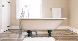 Modern bathroom interior design with clawfoot bath tub and floor tiles. Luxury, contemporary bathrooms, UK.