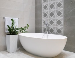 modern bathroom interior design with white stone bathtub, grey tiles wall, ceramic flowerpot with green plant and hanger with towel