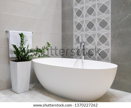modern bathroom interior design with white stone bathtub, grey tiles wall, ceramic flowerpot with green plant and hanger with towel Stock photo ©