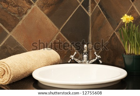 Modern bathroom interior with a wash basin, beige rolled up towel and bright yellow daffodil flowers