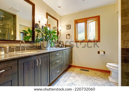 Modern bathroom interior with big cabinet and two mirrors in soft ivory room with tile floor and window