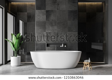 Modern bathroom interior with black tile walls, concrete floor and white bathtub. 3d rendering copy space