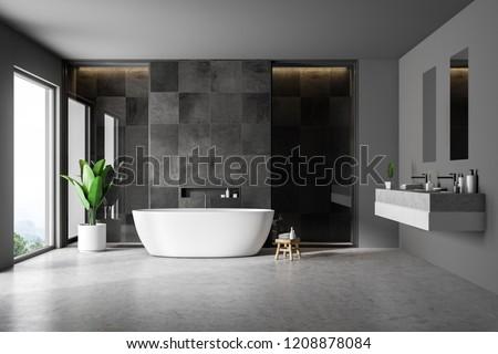 Modern bathroom interior with black tile walls, concrete floor, white bathtub and double sink. Loft window. 3d rendering