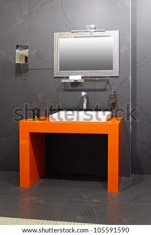 Modern bathroom interior with contemporary orange basin
