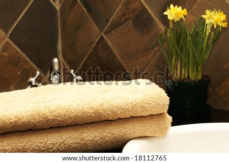 Modern bathroom interior with orange towels lying next to the sink and daffodil flowers