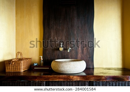 Modern bathroom interior with original white stone sink, clock, wooden baskets and soap dispenser. Wooden interior of spa in yellow and gold colors. Selective focus, only part of bathroom is in focus