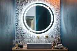 Modern bathroom interior with white wash basin, golden faucet and round illuminated mirror.