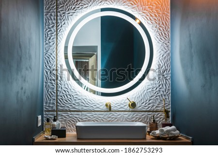 Modern bathroom interior with white wash basin, golden faucet and round illuminated mirror. Photo stock ©