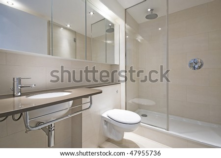 Modern bathroom with a designer wash basin and bath tub in beige
