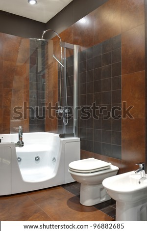 Modern bathroom with brown colored walls and white bath.