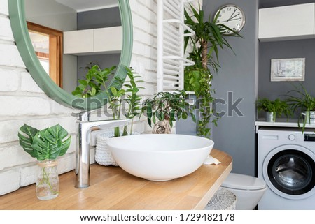 Modern bathroom with ceramic wash basin on wooden couter and green plants in white grey interior. Scandinavian style in apartment. Photo stock ©