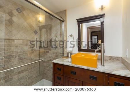 Modern Bathroom with glass shower and counter top in marble with orange square sink
