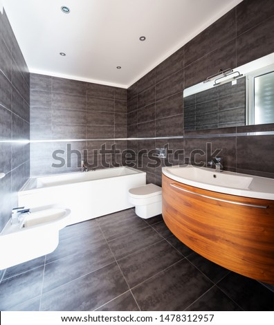 Modern bathroom with gray marble tiles and wooden sink. Nobody inside