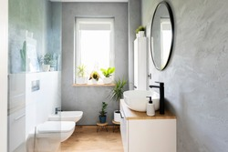 Modern bathroom with grey wall, white furniture and wooden tiles on a floor. Bright interior with window, mirror and stylish washbasin. Minimalism and scandinavian design of washroom.
