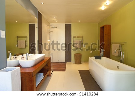 Modern bathroom with pastel coloured walls and white bath There's also a wood floored open shower