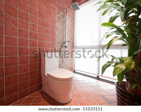 modern bathroom with toilet and green plant