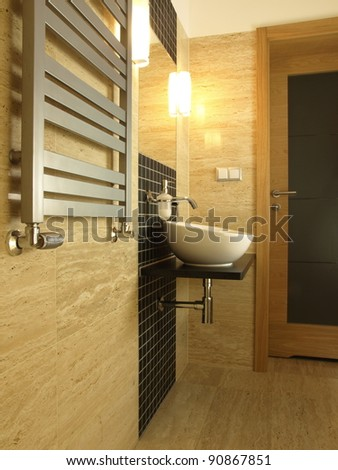 Modern bathroom with vessel sink and travertine tiles.