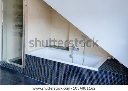 Modern bathroom with white bathtub and shower #1034881162