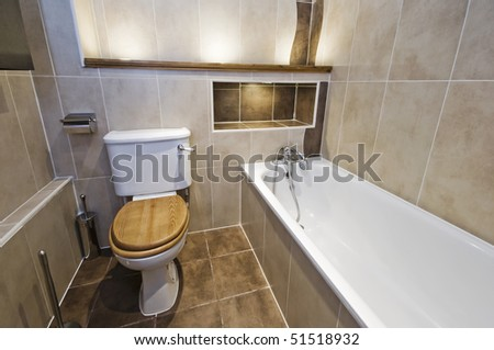 modern bathroom with white ceramic suite and stone tiles