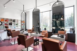 Modern beauty salon with places for makeup artist and hairdresser, big stylish mirrors, pink interior, no people