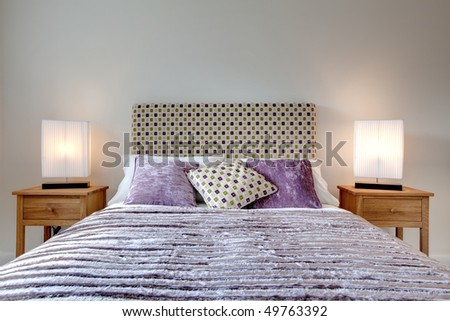 Modern bed dressed with fashionable brightly coloured cushion and quilt, lamps and oak side tables